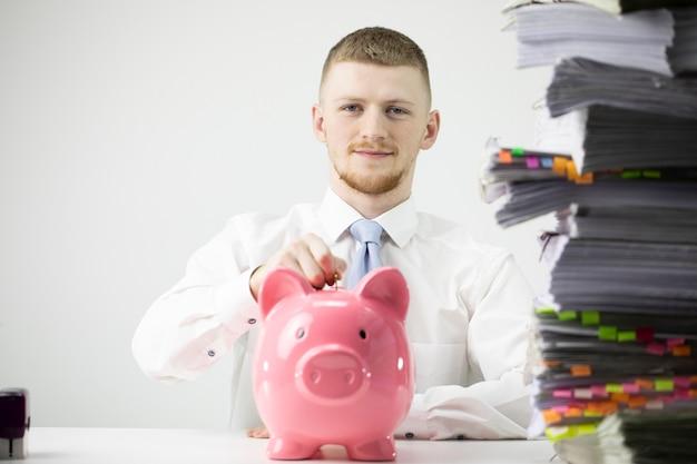 Улыбающийся молодой бизнесмен вставляет монету в копилку