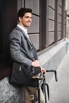 壁に寄りかかって笑顔の青年実業家