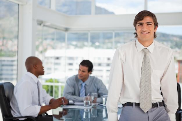 웃는 젊은 사업가 테이블에 기댄 다