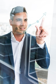 Smiling young businessman pointing finger at increasing graph on transparent glass