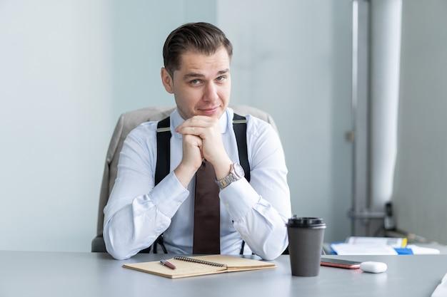 웃고 있는 젊은 사업가가 책상에 앉아 웹캠으로 화상 통화를 하거나 클라이언트와 대화를 나누며 동기가 부여된 남성 코치나 트레이너가 온라인 튜토리얼 촬영, 교육 과정 녹화