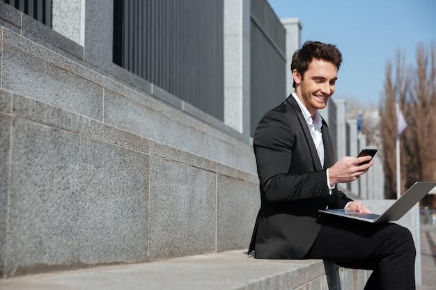 Giovane uomo d'affari sorridente che si siede all'aperto che chiacchiera dal telefono.