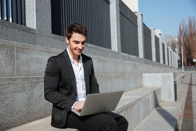 Giovane uomo d'affari sorridente che si siede all'aperto. Foto Gratuite