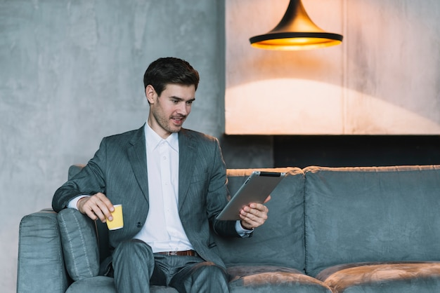 Smiling young businessman sitting on sofa holding coffee cup and digital tablet