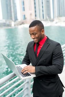 フェンスの上のラップトップで川の近くに立っている笑顔の青年実業家。