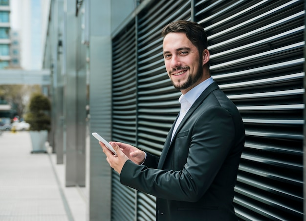 Smiling young businessman standing outside the office building holding mobile in hand