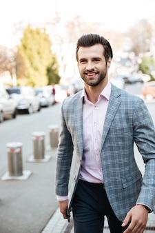 Giovane uomo d'affari sorridente che cammina all'aperto.