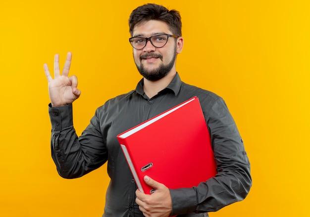 フォルダーを保持し、黄色に分離されたオーケージェスチャーを示す眼鏡をかけている若いビジネスマンの笑顔