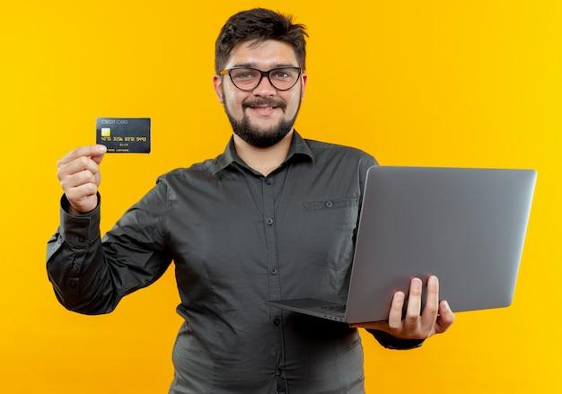 노트북과 신용 카드를 들고 안경을 쓰고 웃는 젊은 사업가