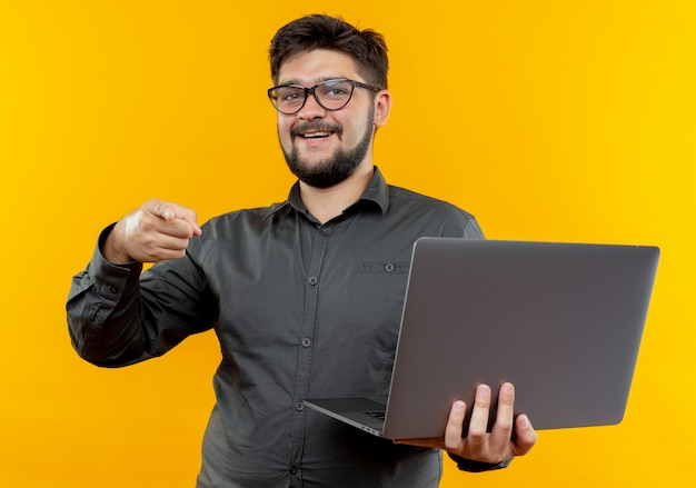 Smiling young businessman wearing glasses holding laptop and points at camera