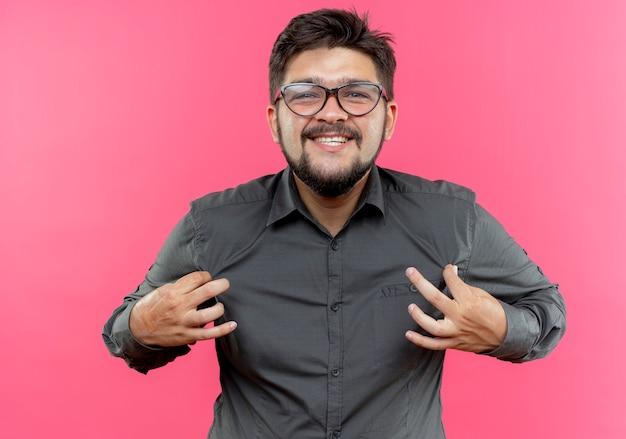 Улыбающийся молодой бизнесмен в очках, держащий рубашку, изолированную на розовой стене