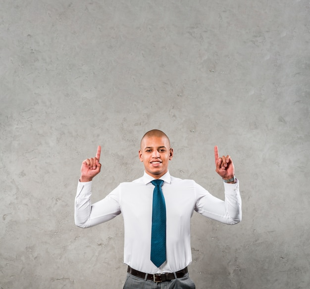Smiling young businessman with his arms raised pointing his finger upward against grey wall