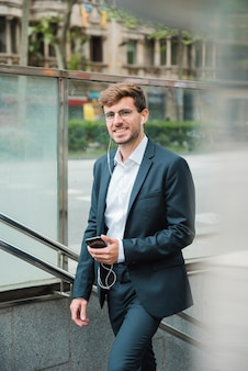 Smiling young businessman with his earphone in ear holding mobile phone in hand