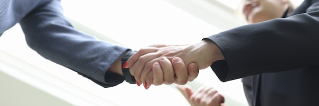 Smiling young businesspeople shaking hands in handshake
