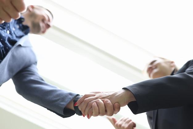 握手で手を振る若いビジネスマンの笑顔
