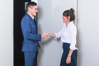 Smiling young businesswoman and businesswoman shaking each other's had