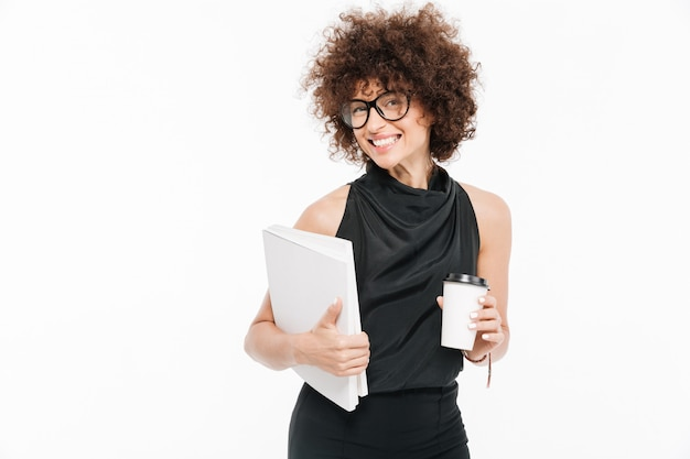 Smiling young businesswoman in eyeglasses holding laptop