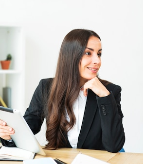 Smiling young businesswoman holding digital tablet in hand looking away