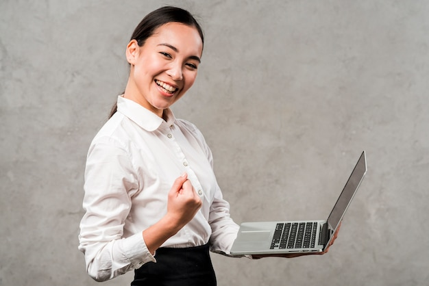 Smiling young businesswoman holding laptop in hand clenching her fist against grey wall