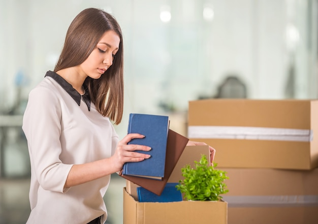 Smiling young businesswoman packing boxes in office.