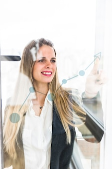Smiling young businesswoman pointing finger at increasing graph on transparent glass
