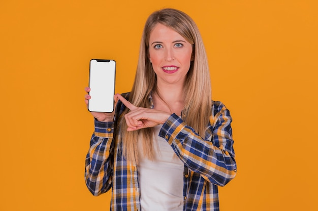 Smiling young businesswoman pointing his finger at mobile phone against an orange background