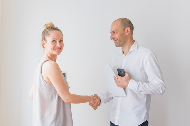 Smiling young businesswoman shaking hand with businessman holding paper and cellphone