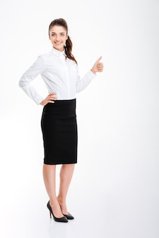 Smiling young businesswoman showing thumb up isolated on a white wall