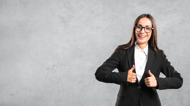 Smiling young businesswoman showing thumb up sign against gray backdrop