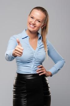Улыбающийся молодой предприниматель показывает палец вверх