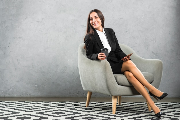 Smiling young businesswoman sitting on armchair holding disposable coffee cup and cellphone