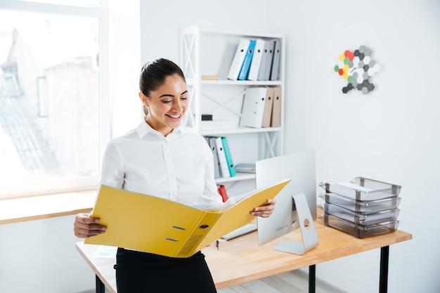 Улыбающийся молодой предприниматель, сидя на столе с документами в офисе