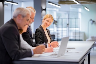 Smiling young businesswoman sitting with businesspeople working at workplace