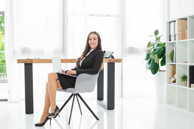 Smiling young businesswoman sitting at workplace with laptop on her lap