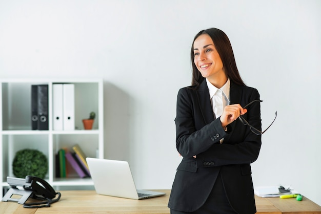 Smiling young businesswoman standing in front of office desk