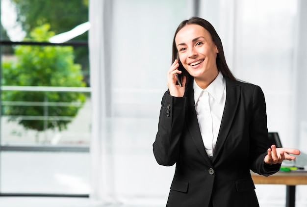 Smiling young businesswoman taking on cellphone gesturing