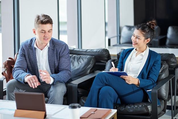 Улыбающийся молодой предприниматель делает заметки в планировщике, разговаривая с коллегой, показывающим презентацию на планшетном компьютере