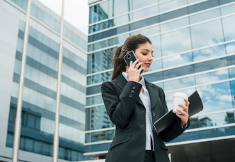 Smiling young businesswoman talking on cell phone standing in front of building