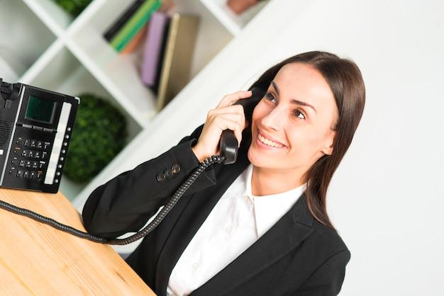 Улыбающаяся молодая деловая женщина разговаривает по телефону в офисе