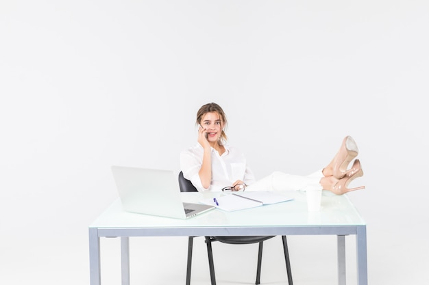Smiling young businesswoman using laptop and writing with legs on desk isolated over white background