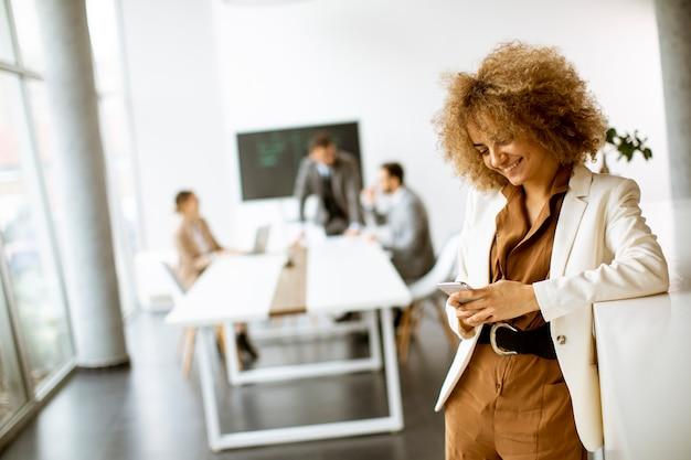 Улыбающийся молодой предприниматель с помощью мобильного телефона в современном офисе Premium Фотографии