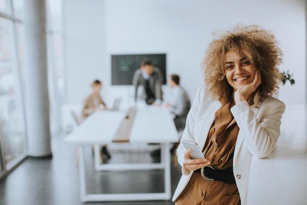 Улыбающийся молодой предприниматель с помощью мобильного телефона в современном офисе