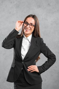 Smiling young businesswoman with her hand on hip standing in front of grey wall
