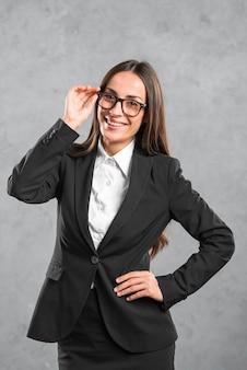 Улыбающаяся молодая деловая женщина с ее рукой на бедре, стоящем перед серой стеной