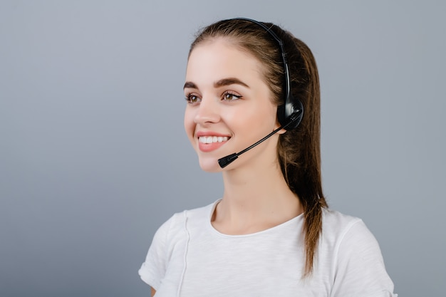 Smiling young call center dispatcher woman wearing headset answering customers isolated over grey