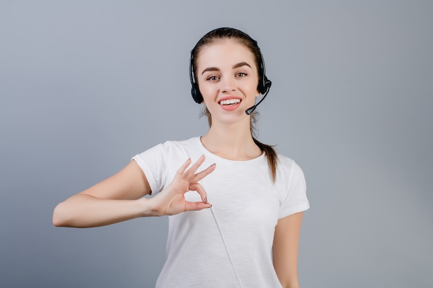 Smiling young call center dispatcher woman wearing headset answering customers showing ok gesture isolated over grey