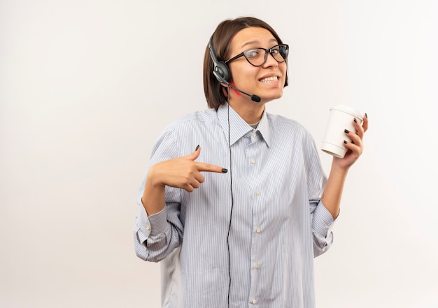 Улыбающаяся молодая девушка колл-центра в очках и гарнитуре держит и указывает на пластиковую кофейную чашку, изолированную на белой стене