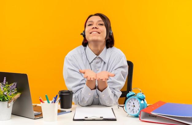 Улыбающаяся молодая девушка колл-центра в гарнитуре сидит за столом, показывая пустые руки спереди, изолированные на оранжевой стене
