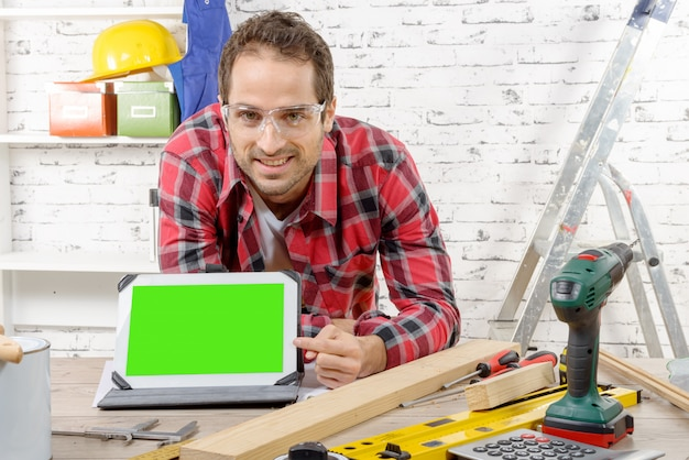 Smiling young carpenter showing green screen on digital tablet