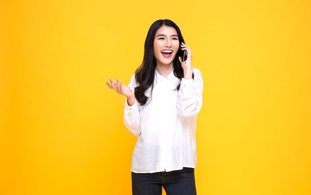 Усмехаясь молодая случайная азиатская женщина говоря умный телефон изолированный над желтым фоном.